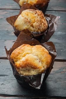 Muffin con i mirtilli, sul vecchio fondo di legno scuro della tavola