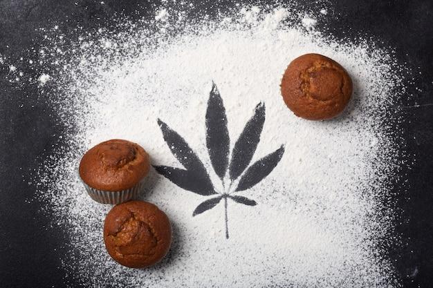 Muffin con cannabis sul tavolo, sfondo scuro. concetto di cibo cdb