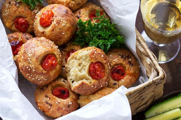 Muffin con formaggio, ricotta e pomodori, verdure e formaggio servito con vino.