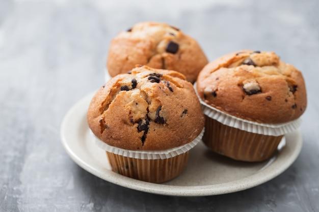 Muffin al cioccolato sul piatto bianco su fondo in ceramica