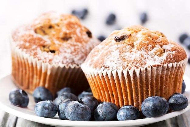 Muffin con mirtilli freschi sulla tavola di legno