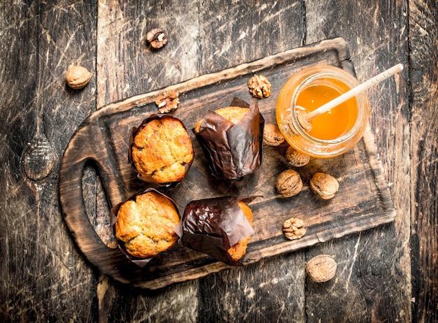 Muffin con miele e noci a bordo sulla tavola di legno.