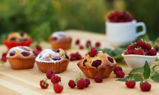 I muffin con lamponi si trovano su un tavolo di legno sullo sfondo di cespugli verdi, intorno a molti lamponi freschi