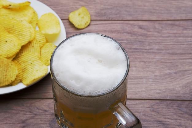 Boccale di birra su un tavolo con patatine
