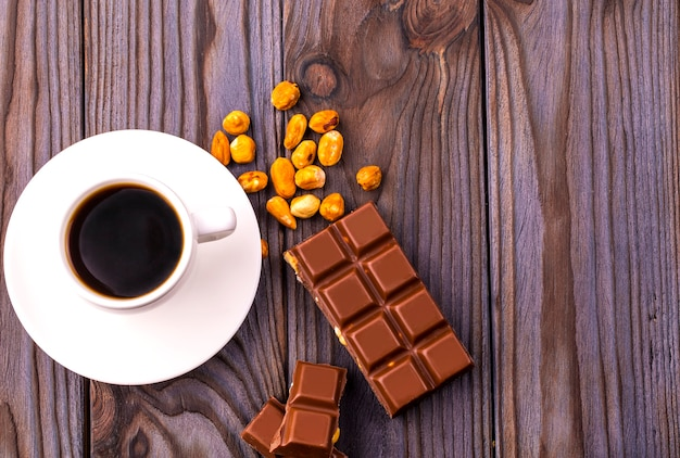 Tazza di caffè e cioccolato con noci su una superficie in legno