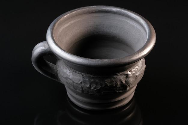 Una tazza da un servizio, piatti di argilla nera su una macro di primo piano muro nero