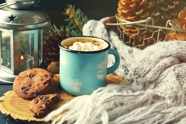 Tazza di cacao caldo con marshmallow, biscotti e lanterna sul tavolo nero