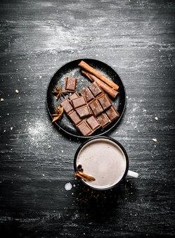 Tazza di cioccolata calda con stecca di cannella e fette di cioccolato fondente ..