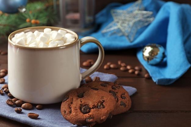 Tazza di cioccolata calda con marshmallow, ramo di abete su fondo di legno