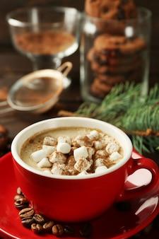 Tazza di cioccolata calda con marshmallow, ramo di abete