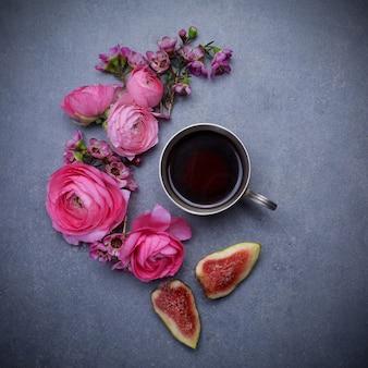 Una tazza di caffè caldo, fichi e fiori.