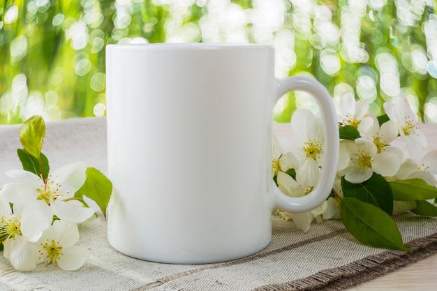Mockup di tazza con fiori di melo primaverili