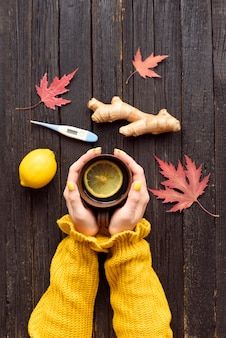 Tazza di tè in mani femminili. limone, zenzero e termometro