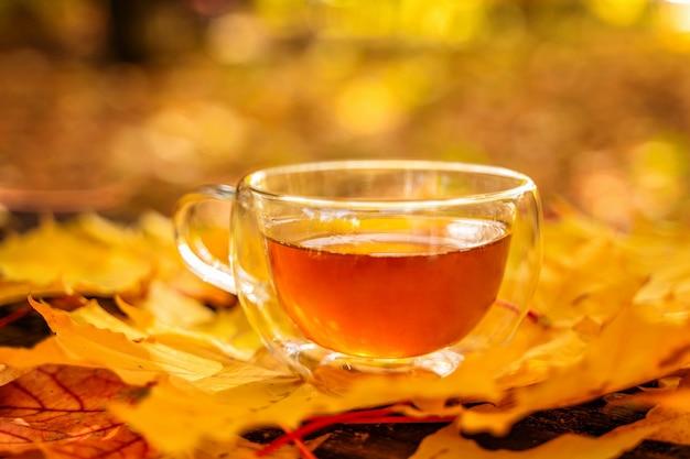 Una tazza di tè si trova su una panchina con foglie autunnali gialle il concetto di un autunno accogliente