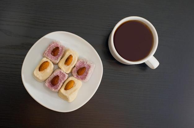 Tazza di tè e delizia turca con mandorle su un piatto