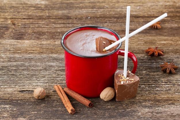 Tazza con cioccolata calda e spezie su tavola di legno