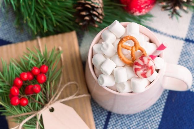 Una tazza con marshmallow vicino a una scatola regalo e un ramo di un albero di natale decorazioni per le vacanze di capodanno