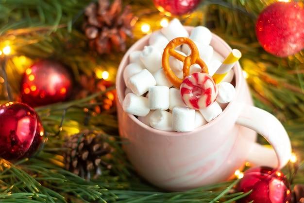 Una tazza con caramello pretzel marshmallow e paglia sullo sfondo di un ramo di un albero di natale