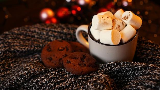 Tazza con marshmallow e biscotti con scaglie di cioccolato su sfondo scuro di natale con palle e luci di natale sfocate