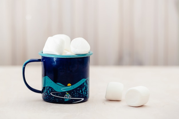 Tazza con gustosi marshmallow sul tavolo in legno chiaro, primo piano. concetto di sfondo cibo invernale.