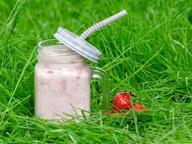 Tazza di yogurt e fragola su uno sfondo di erba verde, spazio per il testo