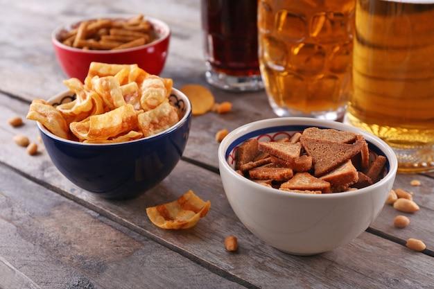 Boccali di birra e ciotole con spuntini sulla tavola di legno