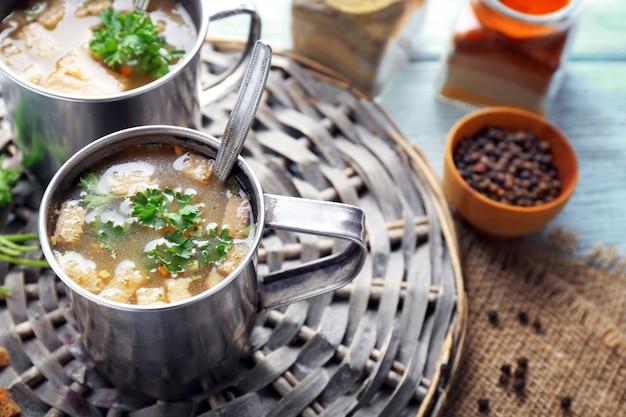 Tazze di zuppa su stuoia di vimini