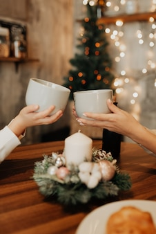 Tazze con tè sullo sfondo di un albero di natale. capodanno e natale. i regali