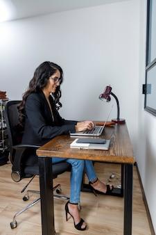 Mujer ejecutiva latina trabajando en su ordenador porttil desde casa debido a la cuarentena