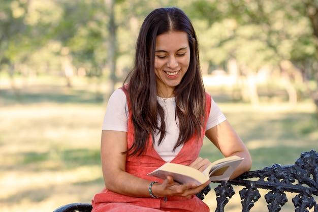 Mujer latina sentada en una banca de un parque leyendo un libro Foto Premium