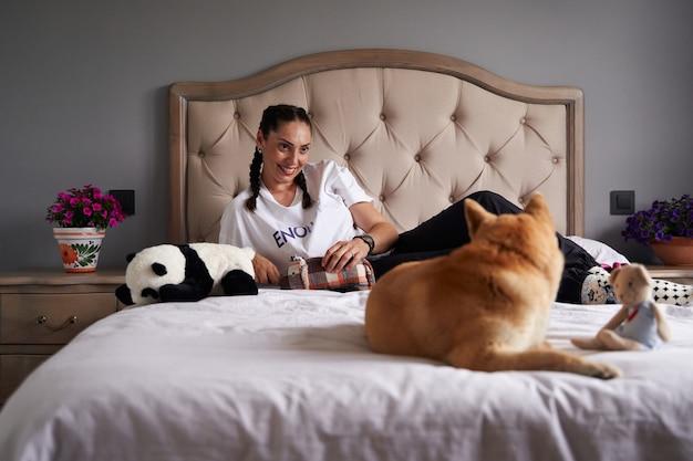 Mujer y su mascota mirandose en la cama
