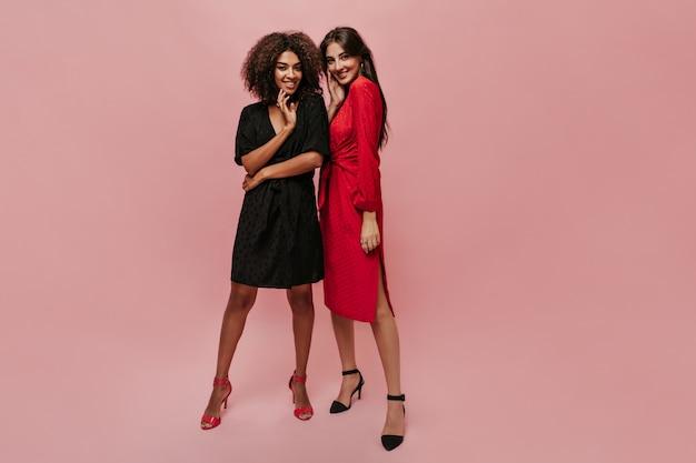 Bella ragazza mulatta in abito scuro a pois e tacchi luminosi che sorride, guarda in camera e posa con una ragazza alla moda in abiti rossi
