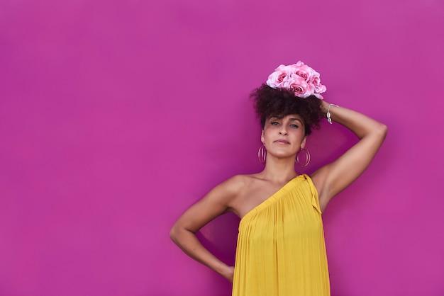La donna mulatta con i capelli afro indossa un abito giallo