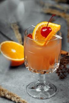 Vin brulè in bicchieri di vetro con mele arancia e cannella. bevanda calda di natale su un tavolo grigio