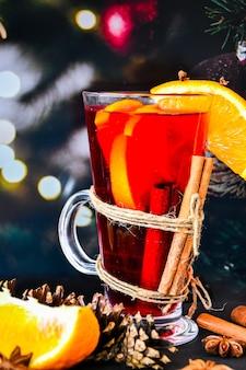 Vin brulé bevanda calda di natale con spezie su uno sfondo scuro. fette d'arancia, bastoncini di cannella, coni natalizi, bokeh luminoso. atmosfera di vacanza, stile rustico. l'idea per creare biglietti di auguri