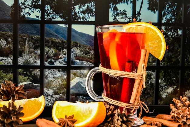 Vin brulè bevanda calda di natale con spezie su un davanzale, accanto alla finestra. fette d'arancia, bastoncini di cannella, pigne. atmosfera di vacanza, stile rustico. l'idea per creare biglietti di auguri