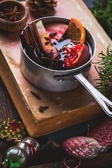 Bevanda calda vin brulè con agrumi, mela, melograno e spezie in casseruola di alluminio con giocattoli vintage dell'albero di natale e ramo di abete su una superficie di cemento