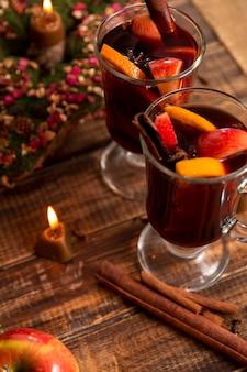 Vin brulè vicino alla candela con frutta e spezie sulla tavola di legno.