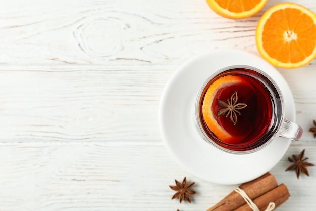Vin brulé, arancia e cannella sulla tavola di legno bianca, vista superiore