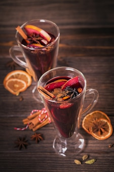 Vin brulè con frutta, bastoncini di cannella e anice su fondo di legno scuro. bevanda riscaldante invernale con ingredienti della ricetta.