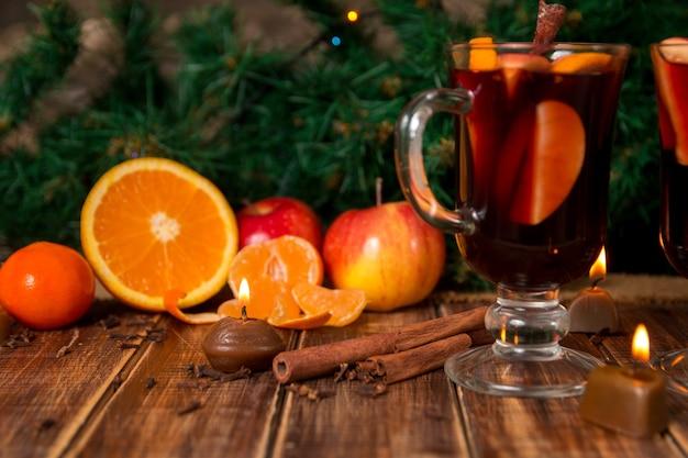Vin brulè con frutta e spezie sulla tavola di legno