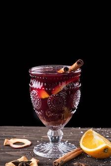 Vin brulè con spezie e frutta su fondo in legno