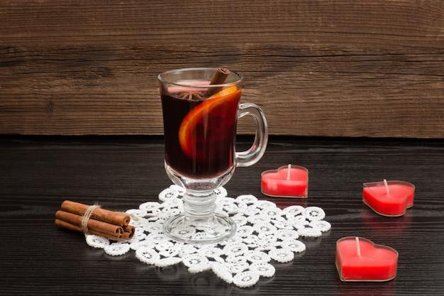 Vin brulè con spezie su un tovagliolo di pizzo. candele a forma di cuore e bastoncini di cannella. sfondo di legno