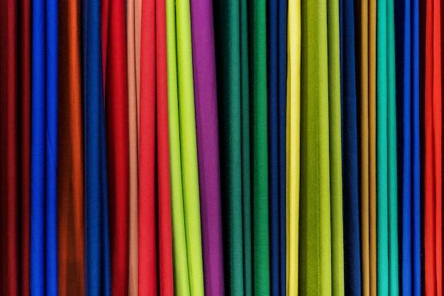 Campioni di tessuto a maglia multicolore in posizione verticale. trama tessuta e sfondo.