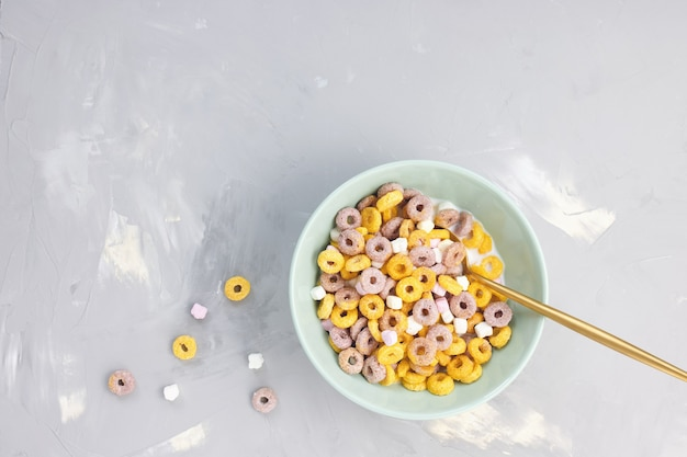 Anelli di frutta di cereali multicolori e latte nell'arco cucchiaio d'oro sfondo grigio vista dall'alto spazio copia