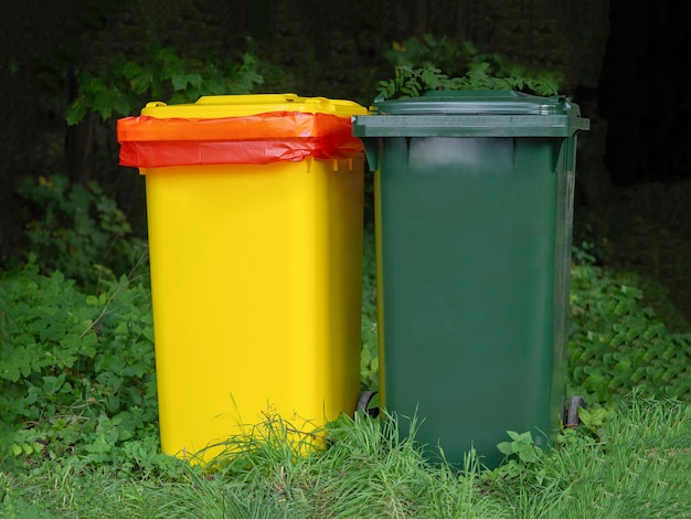 Contenitori multicolori per la raccolta differenziata dei rifiuti in un luogo verde.