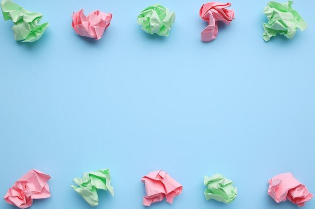 Sfere di carta sgualcite multicolori su sfondo blu.