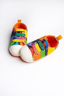 Scarpe sportive in denim multicolore per bambino, si erge su uno sfondo bianco. il concetto di abbigliamento per bambini.