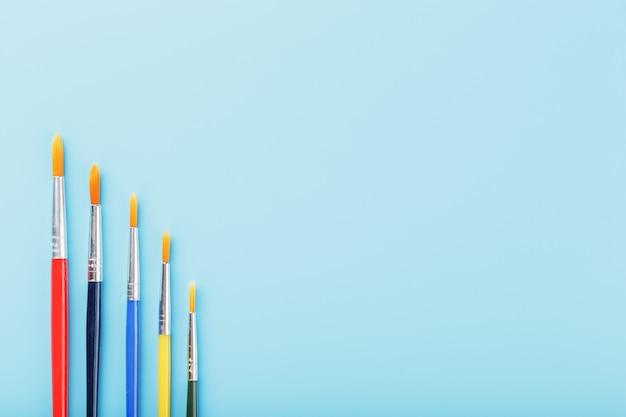 Pennelli multicolori su una priorità bassa blu.