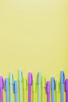 Penne multicolori su giallo con spazio libero.